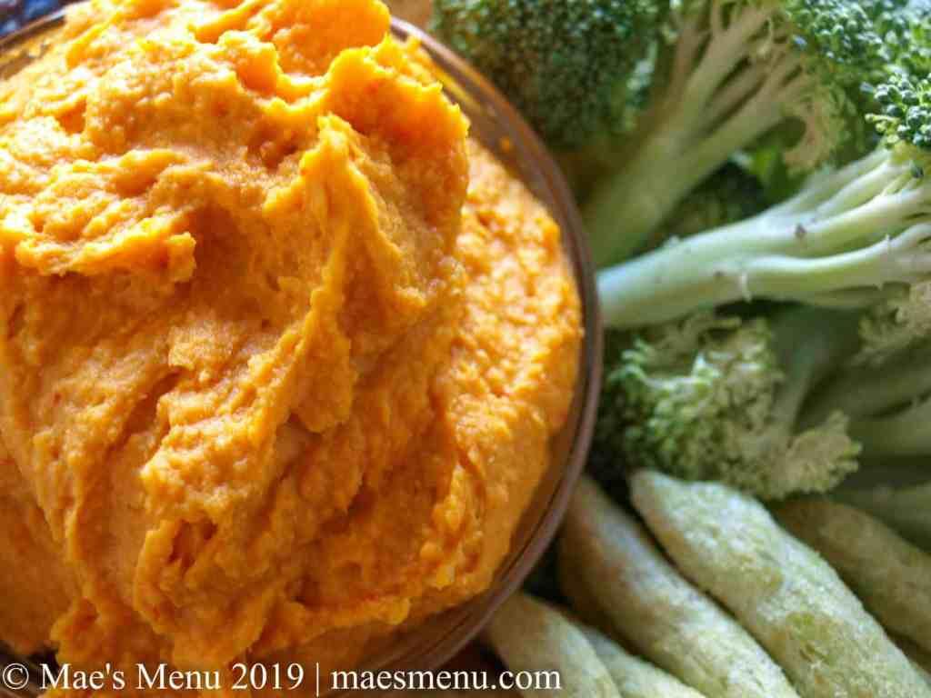 Dish of sweet potato harissa hummus surrounded by veggies and crackers.