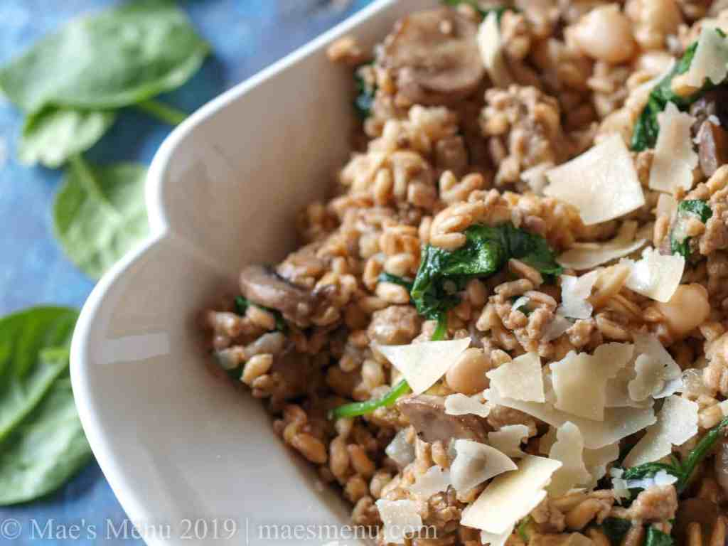Large serving bowl of mushroom farro risotto on a blue table.