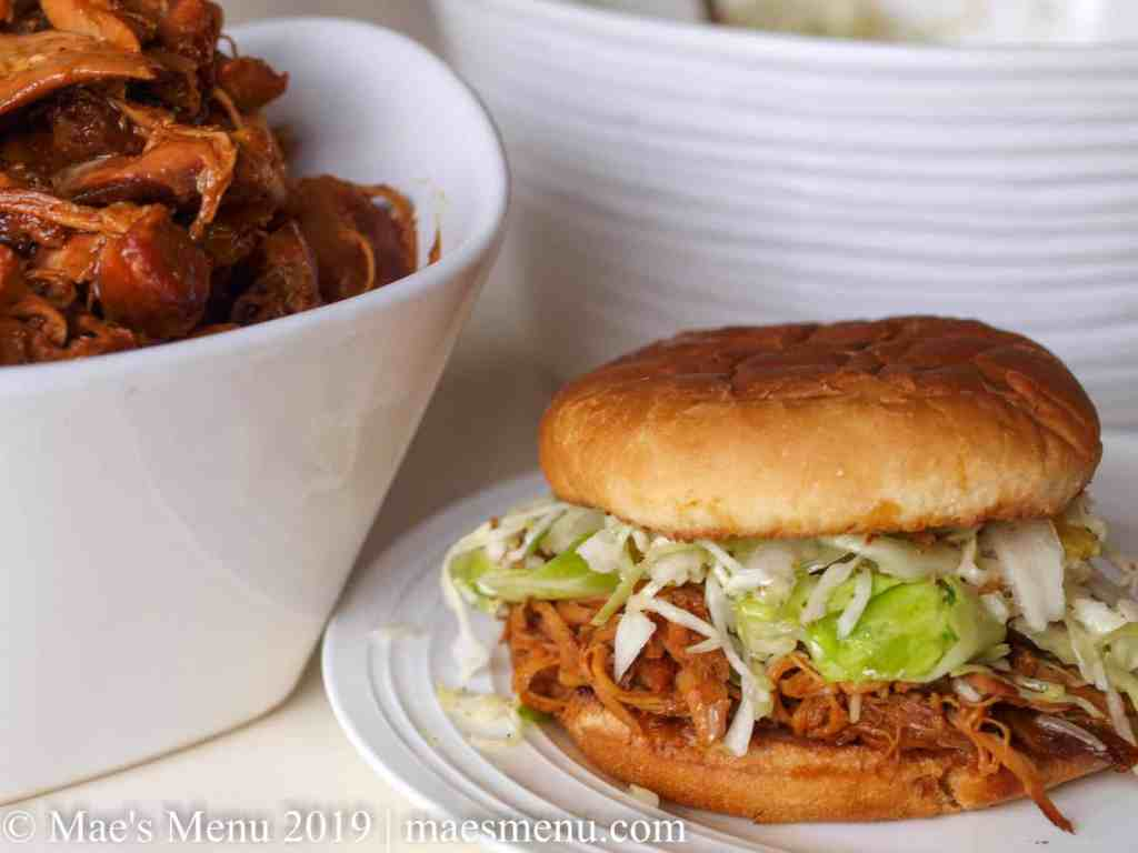 Bowl of honey BBQ crockpot chicken next to a honey BBQ crockpot chicken sandwich.