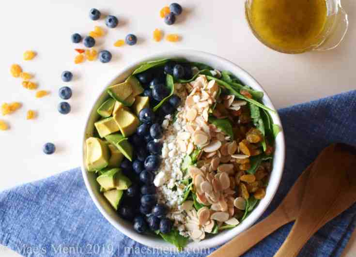 White Bowl of Blueberry & Avocado Spinach salad next to salad tongs & lemon poppy seed dressing.