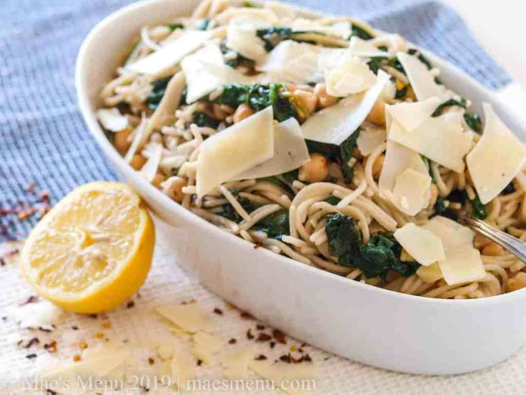 White serving bowl of Spaghetti with Beans & Garlicky Greens next to a lemon, red pepper, and shaved cheese.