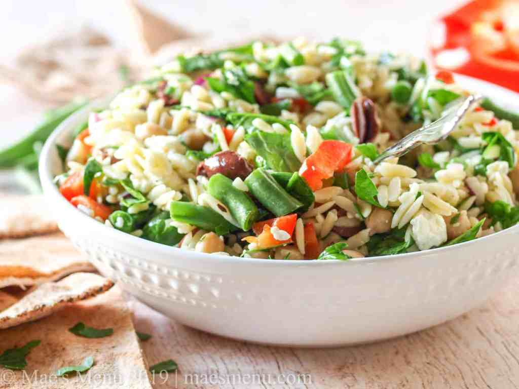 A side shot of a white bowl of chickpea and orzo pasta.