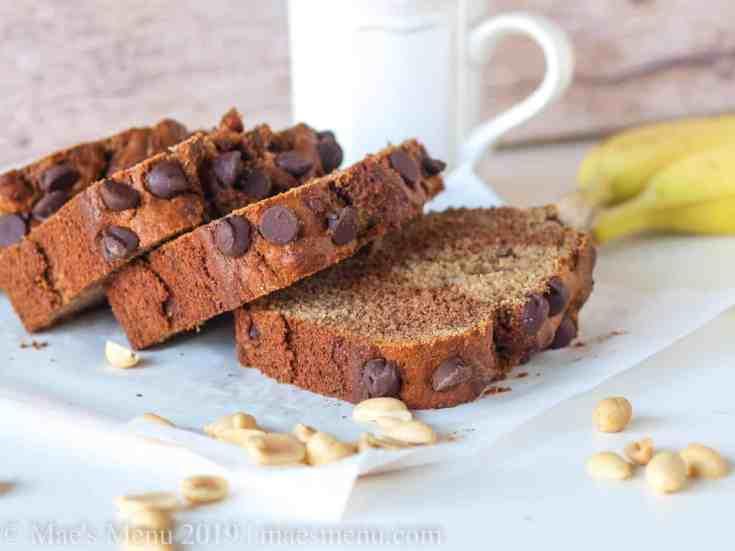 Marbled Peanut Butter & banana Bread by a mug of tea, nuts, and a banana.