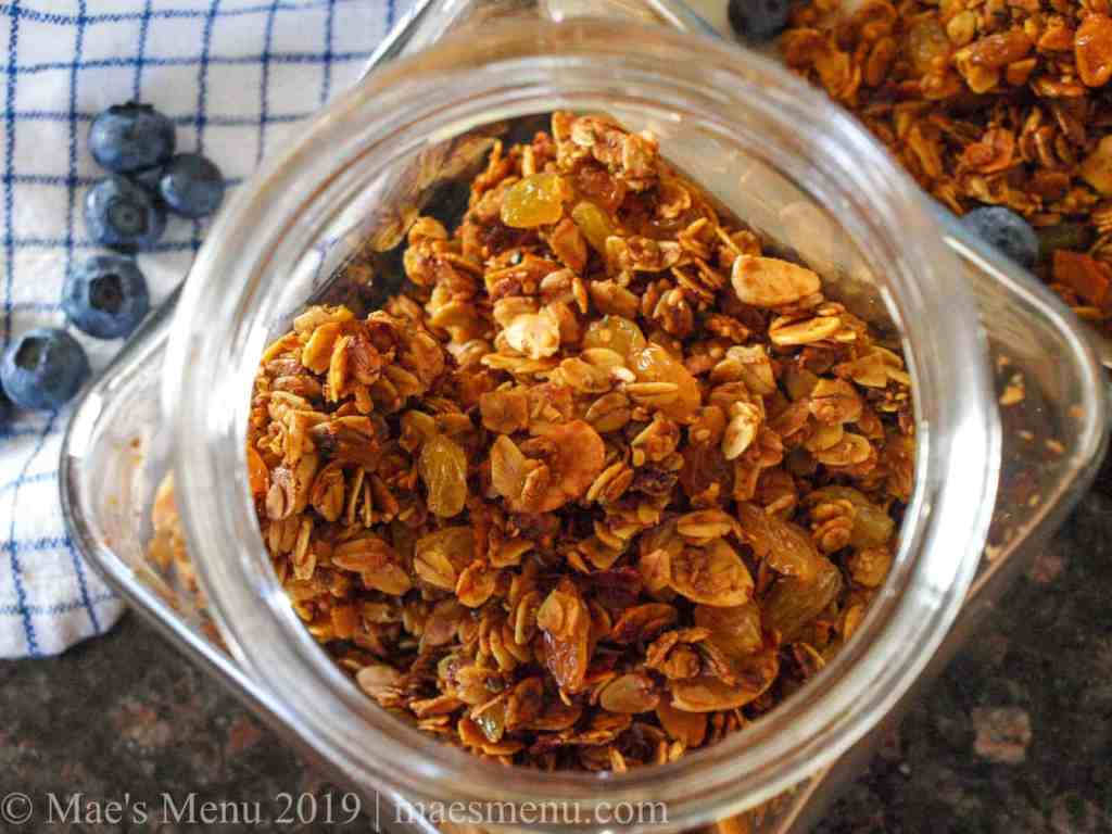 A glass canister of crunchy turmeric granola.