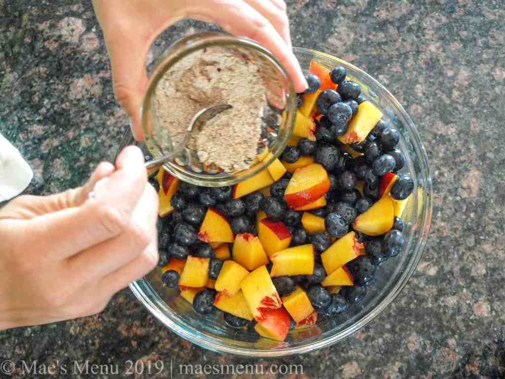 Pouring the flour and spices mixture into the bowl of blueberries and peaches.