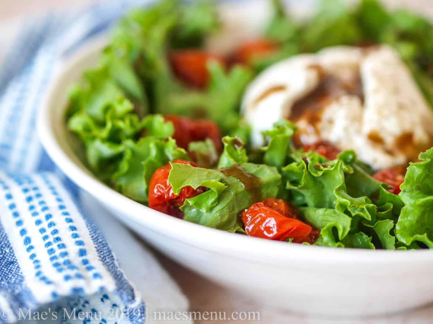 Up-close side shot of roasted tomato salad with burrata.