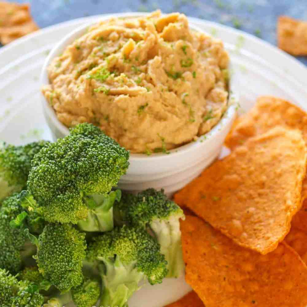 A small crock of curry hummus with sweet potato chips and broccoli.