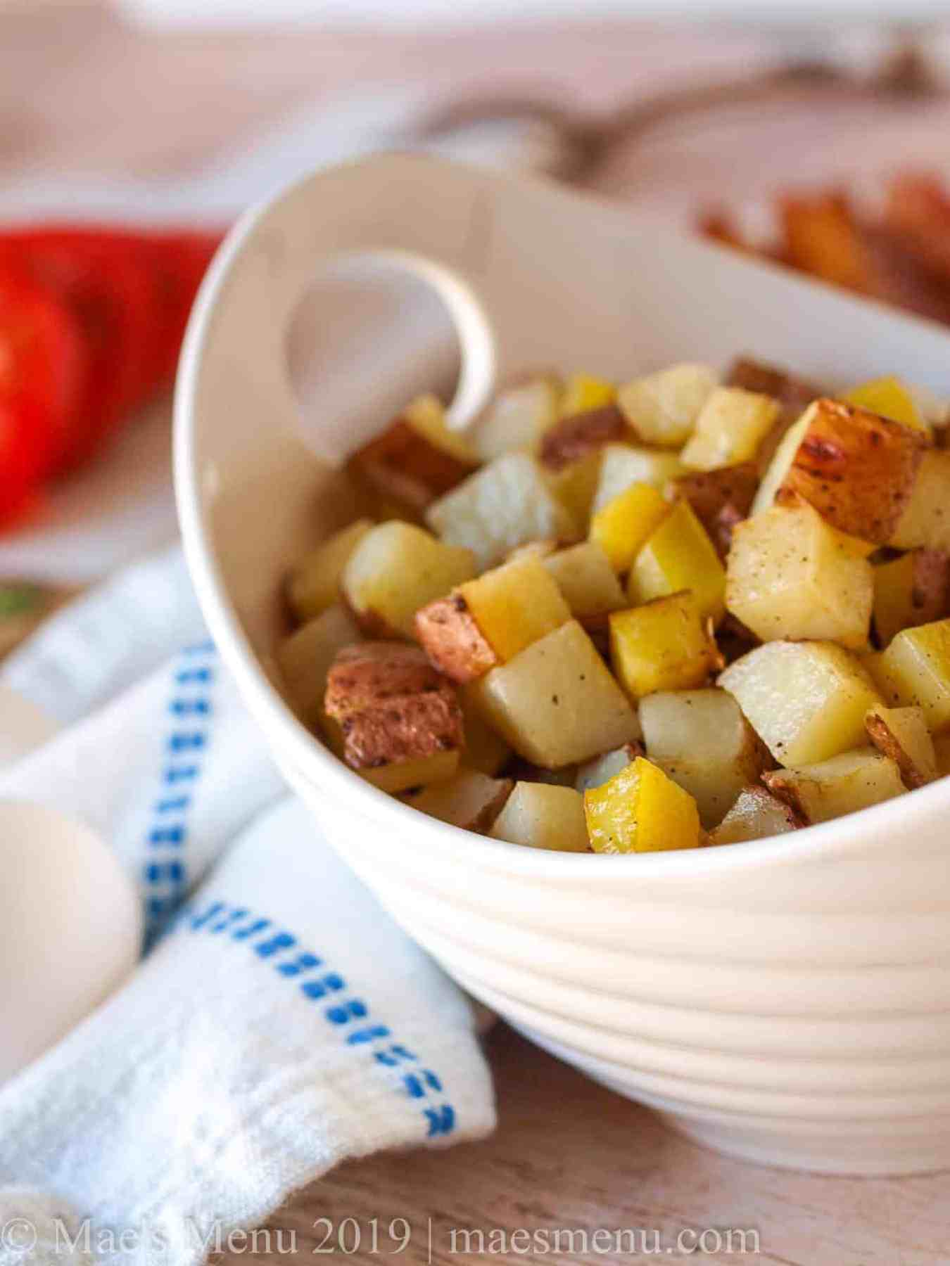 A large white bowl of roasted cubed hash browns.