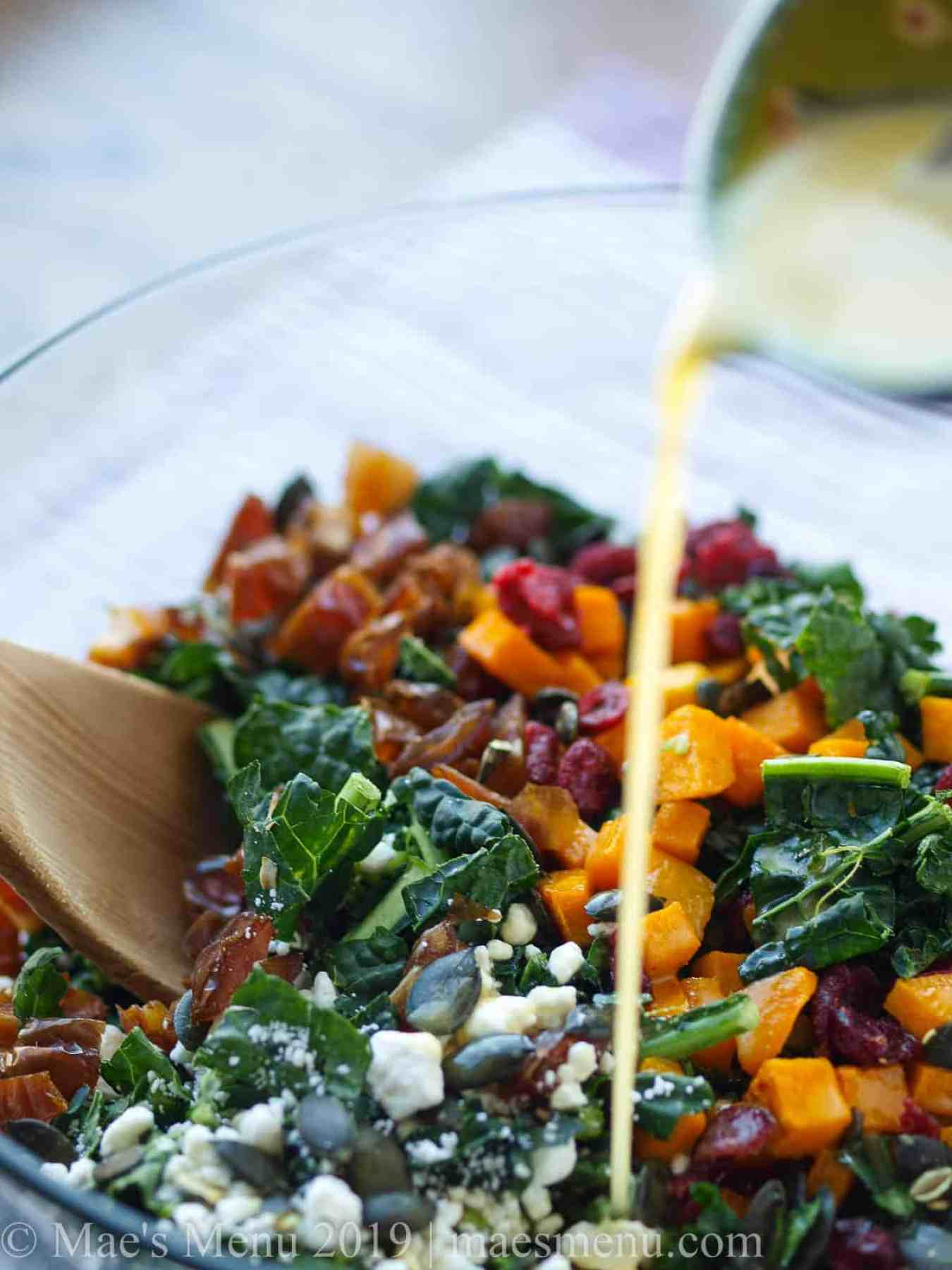 Holiday lacinato kale salad with citrus agave dressing drizzling over.