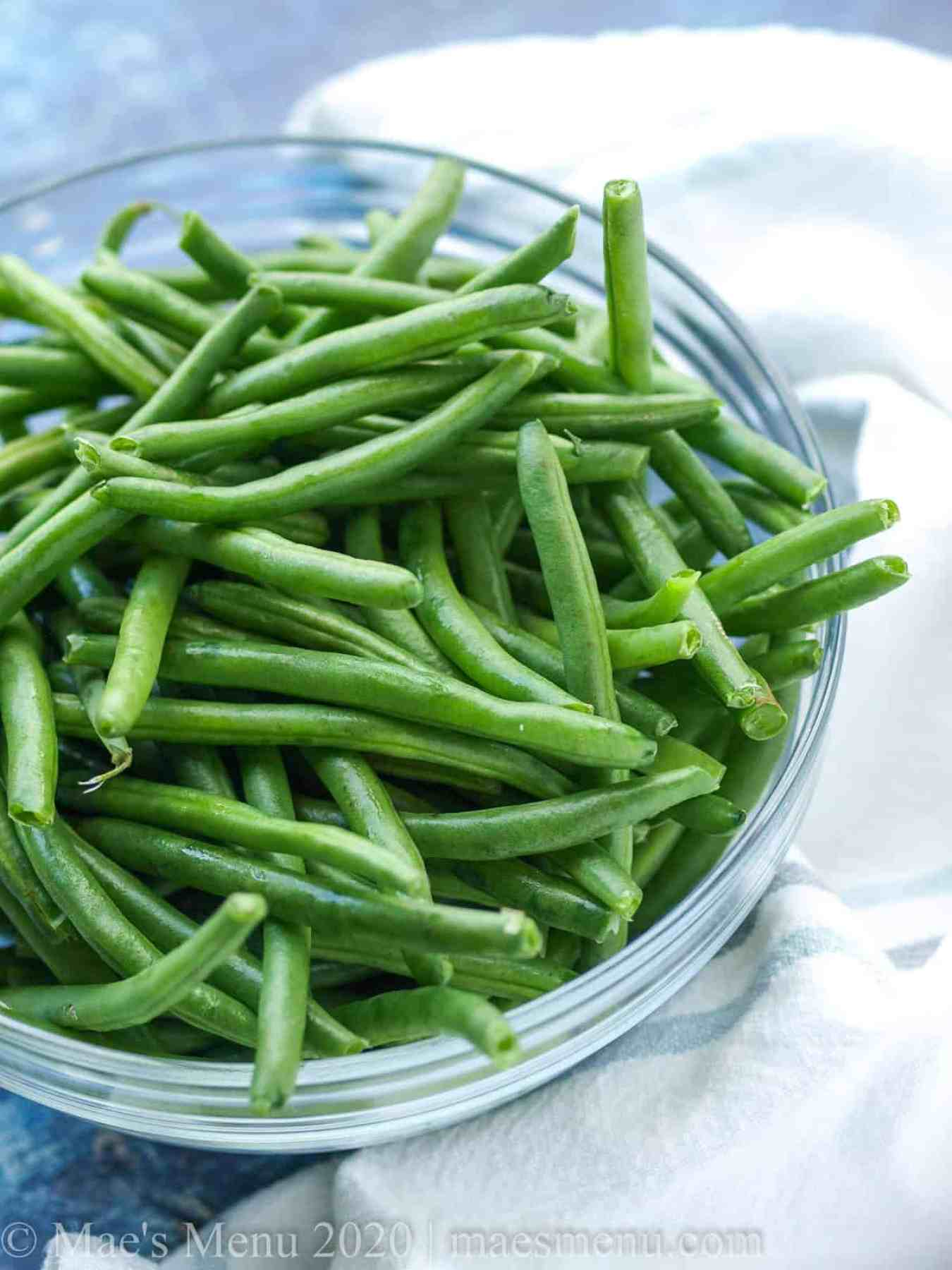 A large bowl of raw green beans.