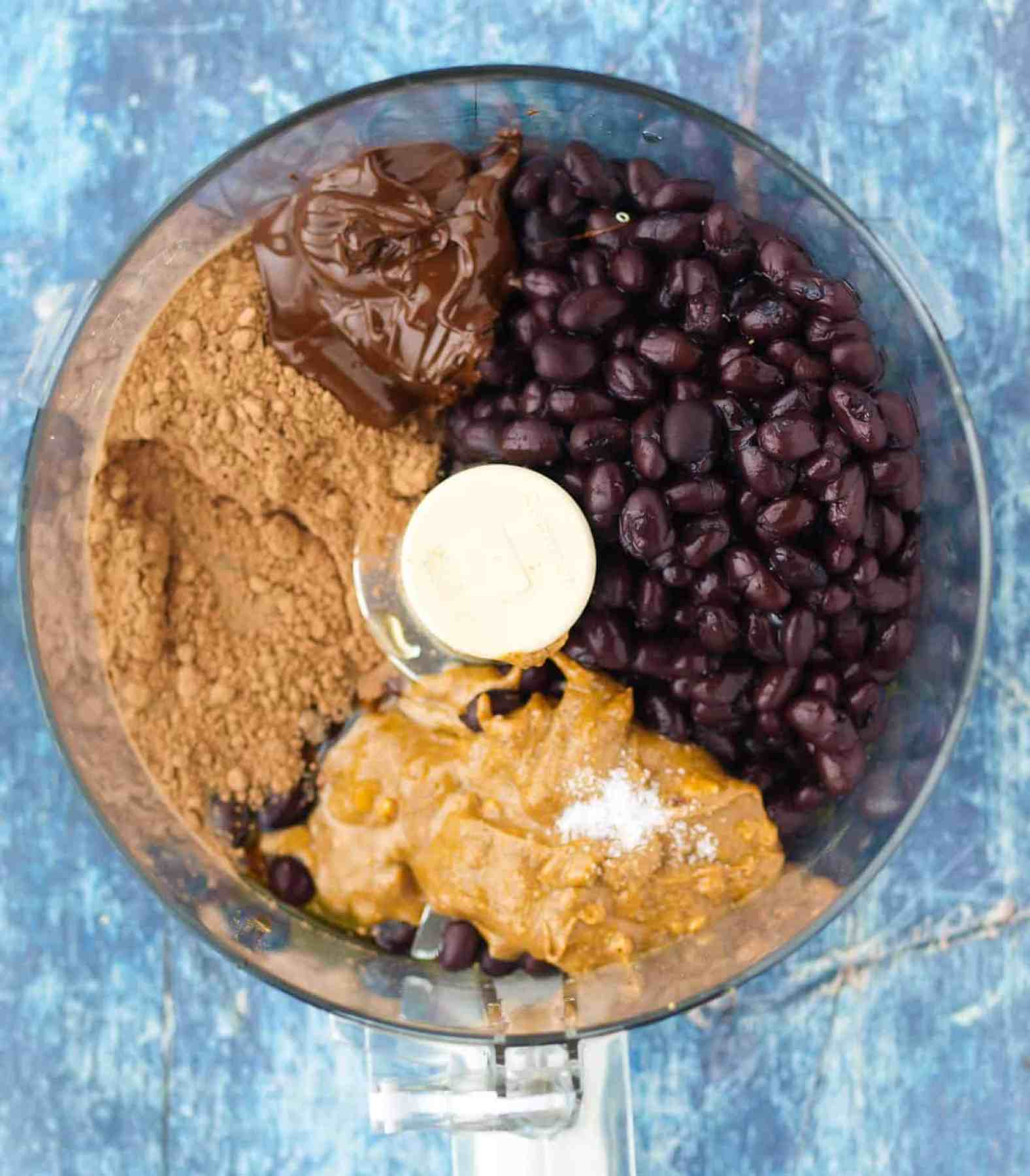 A food processor bowl full of ingredients for Chocolate Hummus.