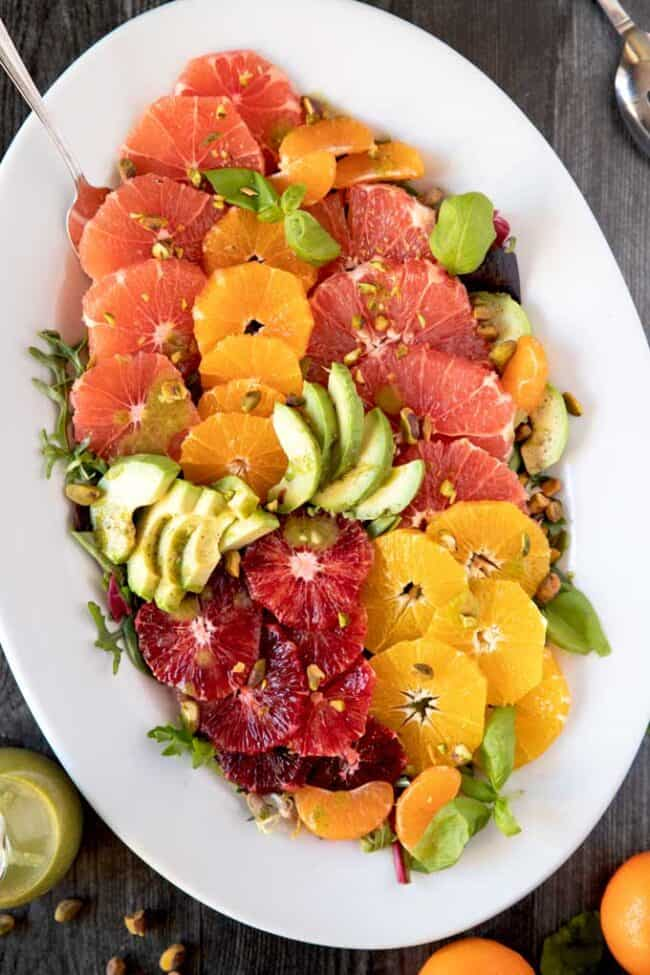 A large white platter of orange and grapefruit slices with avocado, pistachios, and baby basil leaves.