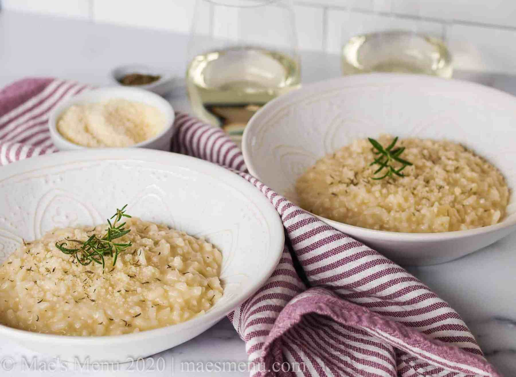 Two white bowls of risotto next to glasses of white wine, parmesan cheese, and a purple striped towel