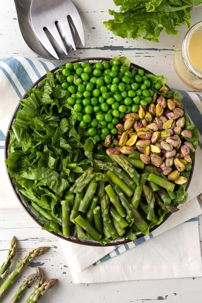 A large bowl of greens covered with green peas, pistachios and asparagus. Next to the bowl sits salad tongs, a blue and white towel, more salad greens, and a cup of dressing.