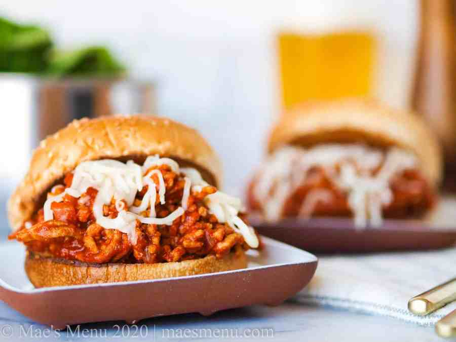 Two plates of sloppy joes on a dish towel with a pepper mill, a glass of beer, and a dish of salad in the background.
