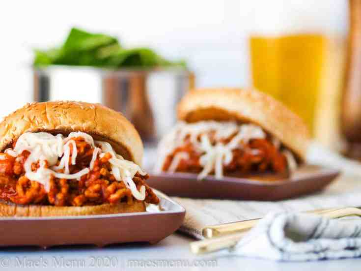 Two turkey sloppy joes on small plates with a glass of beer and a salad behind it.