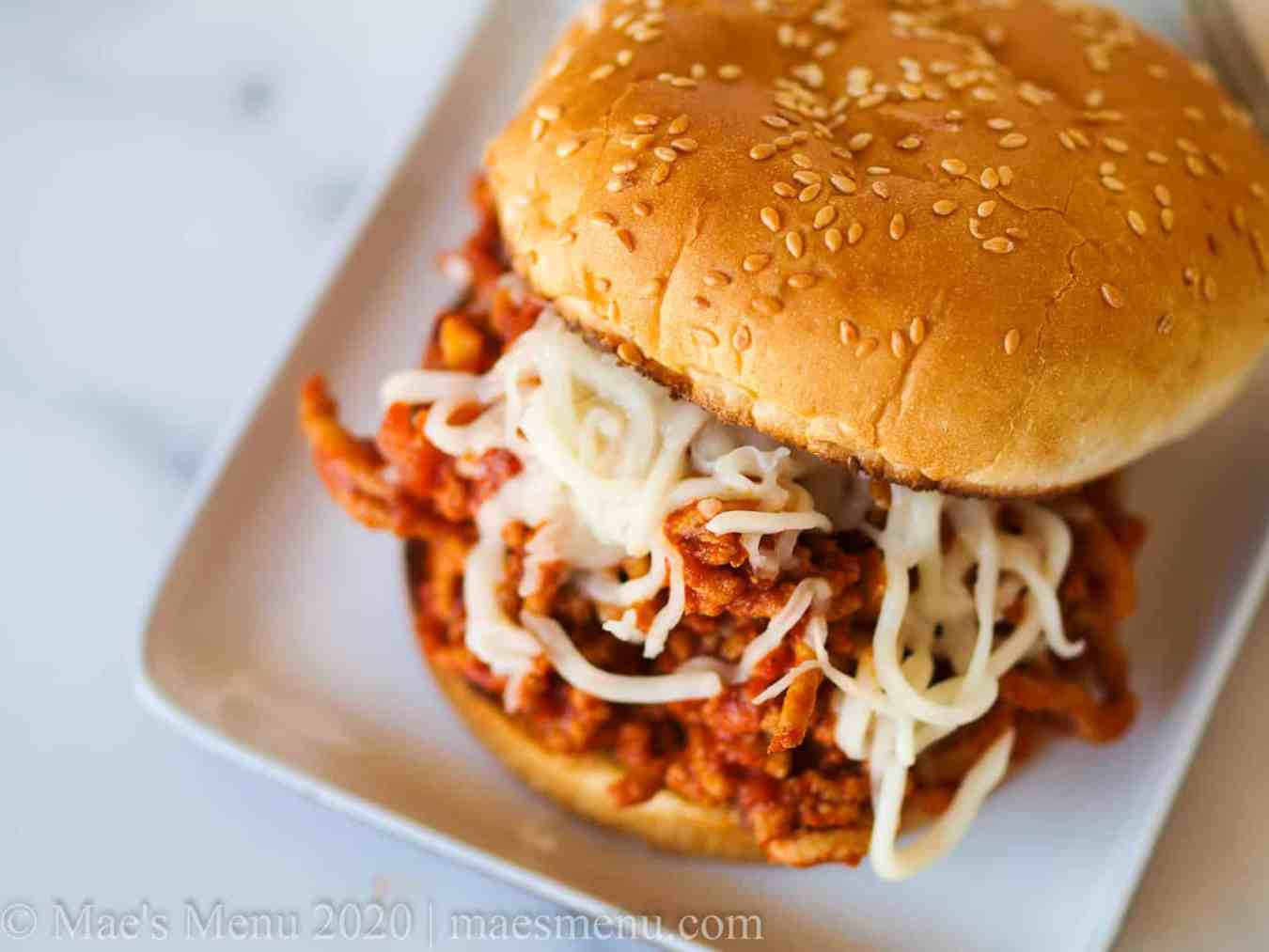 A sloppy joe with shredded cheese on top on a white plate.