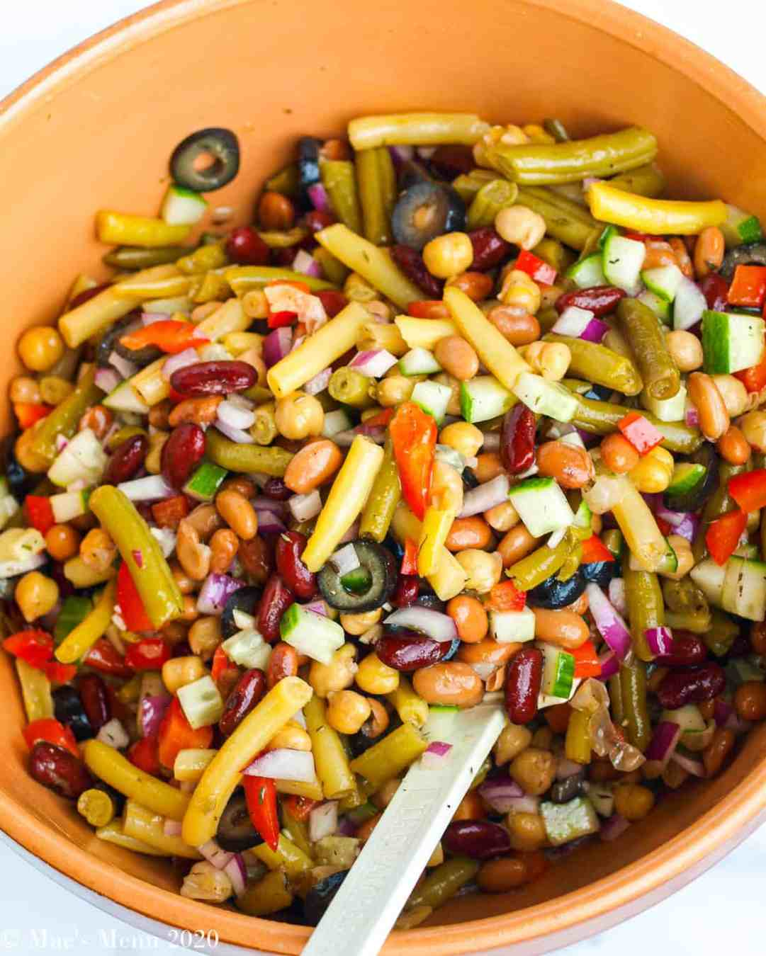 A large mixing bowl of 5 bean salad with a rubber spatula in it.