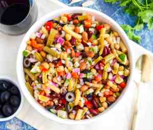 A large bowl of five bean salad with a dish of olives, a spoon, herbs, and a glass of wine next to it.