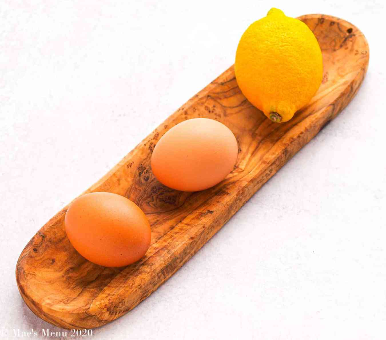 Two eggs and a lemon on a small & long wooden tray.