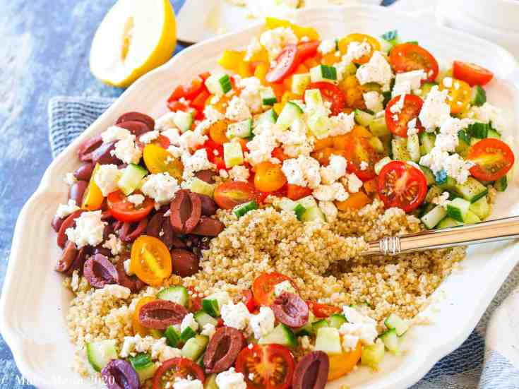 A large white platter of Greek Quinoa Salad with a serving spoon in the salad. A lemon sits behind the plate.