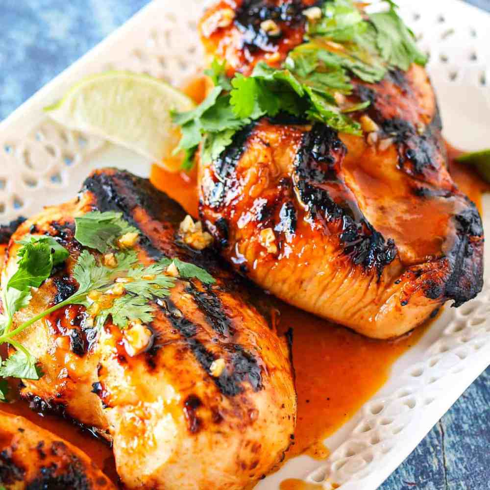 A small white platter of grilled chicken breasts on a blue background. THe chicken is sprinkled with cilantro and has a spicy red marinade sauce over it.