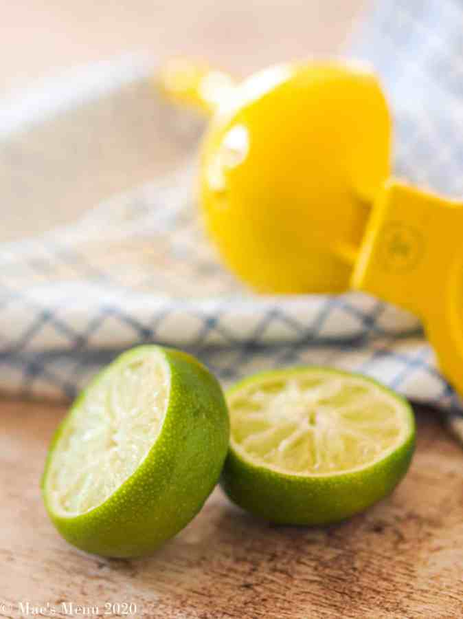 A lime ut in half in front of a citrus juicer.