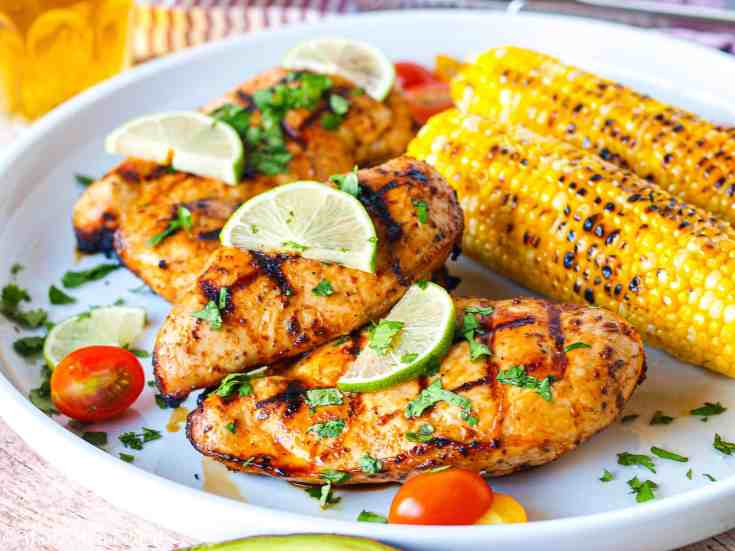 A large white platter with grilled chicken breasts covered in cilantro and limes next to grilled corn
