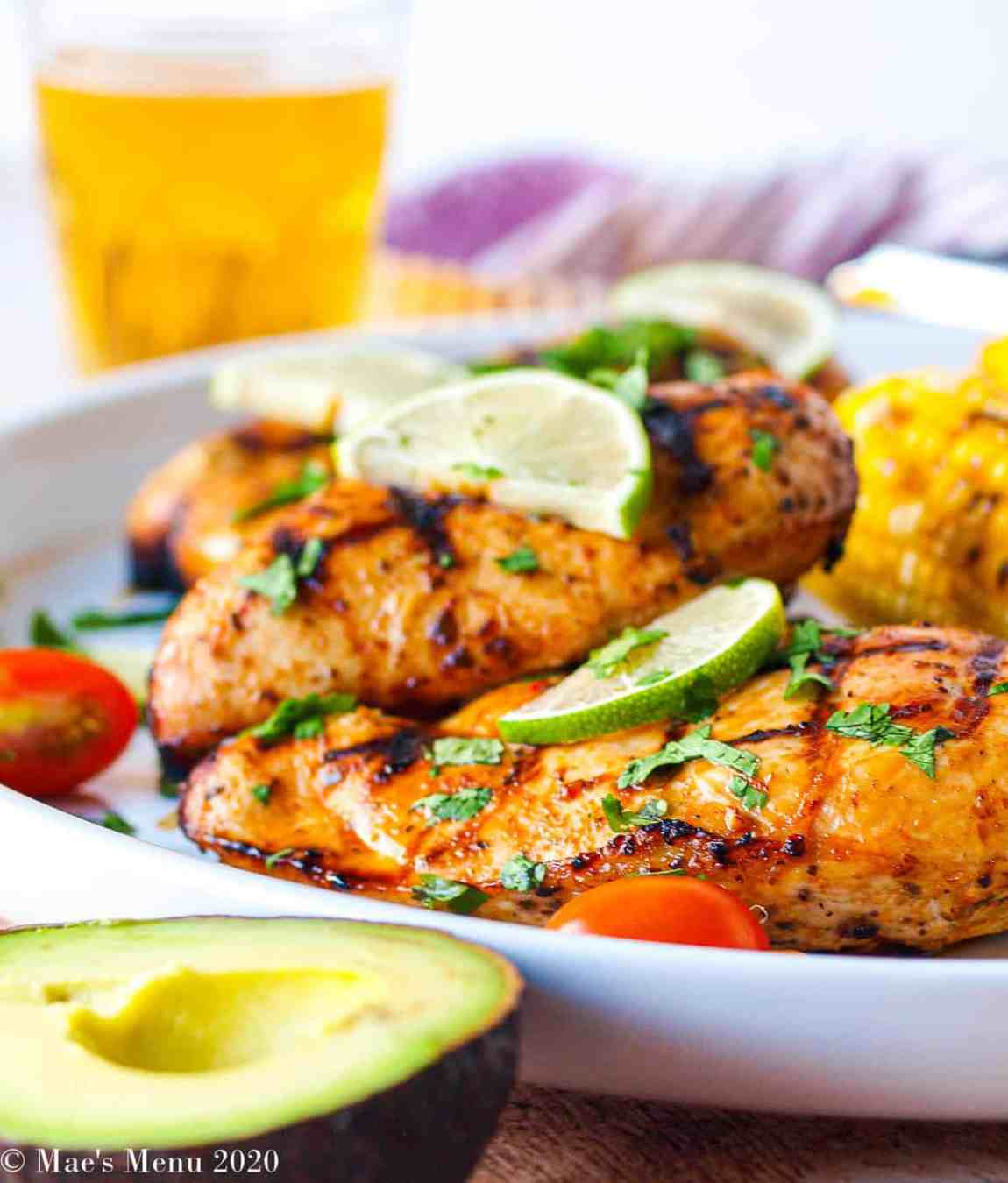 A side shot of a large white platter with grilled chicken breasts on it. In front of the platter sits a half of an avocado. On front of the chicken sits the lime slices and sliced cilantro.