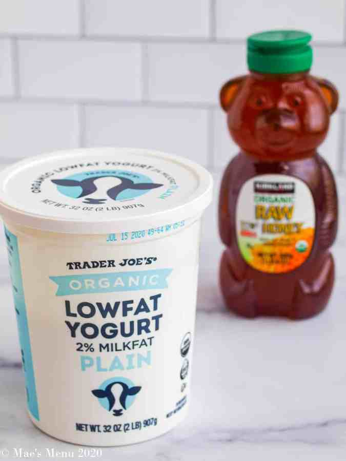 A container of Trader Joe's organic low fat yogurt in front of a bear container of organic raw honey.