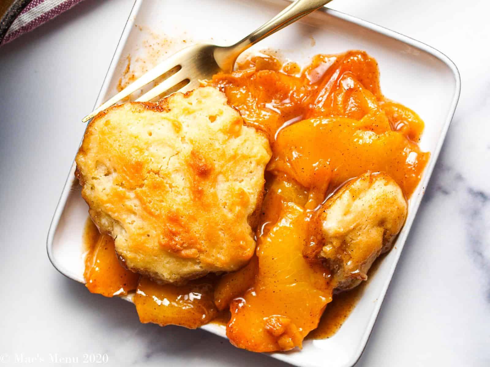 An overhead shot of a small dish of gluten-free peach cobbler on it.