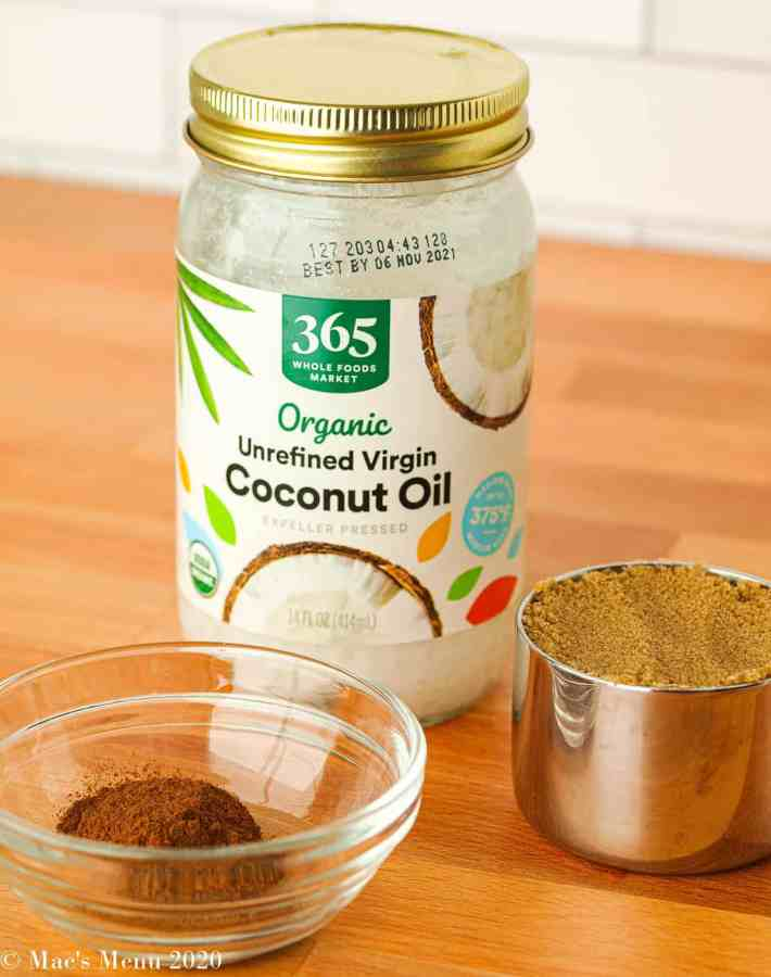 A jar of coconut oil, small measuring cup of dark brown sugar, and a small clear dish of cinnamon and spices.