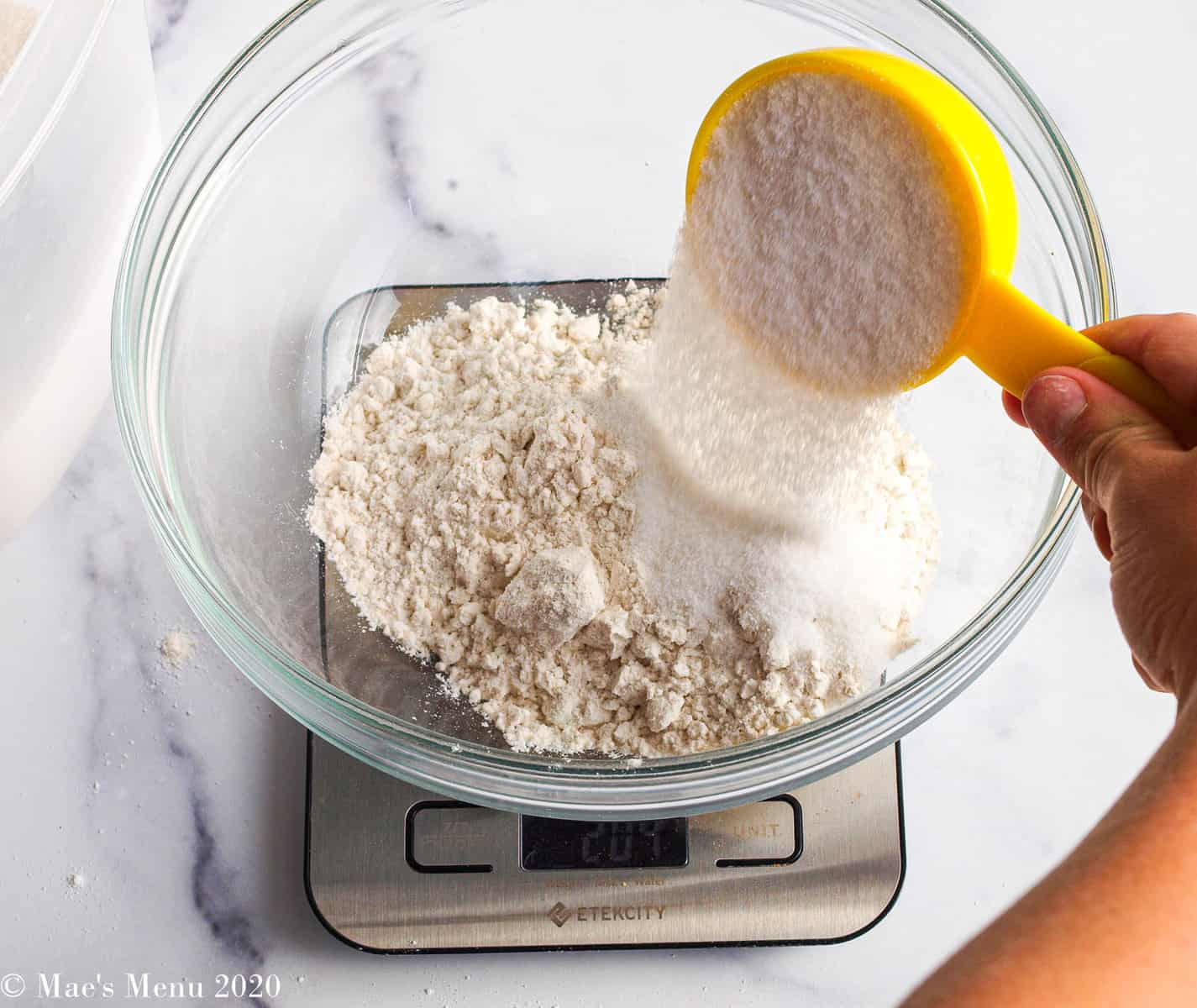 Pouring sugar into the flour in the bowl
