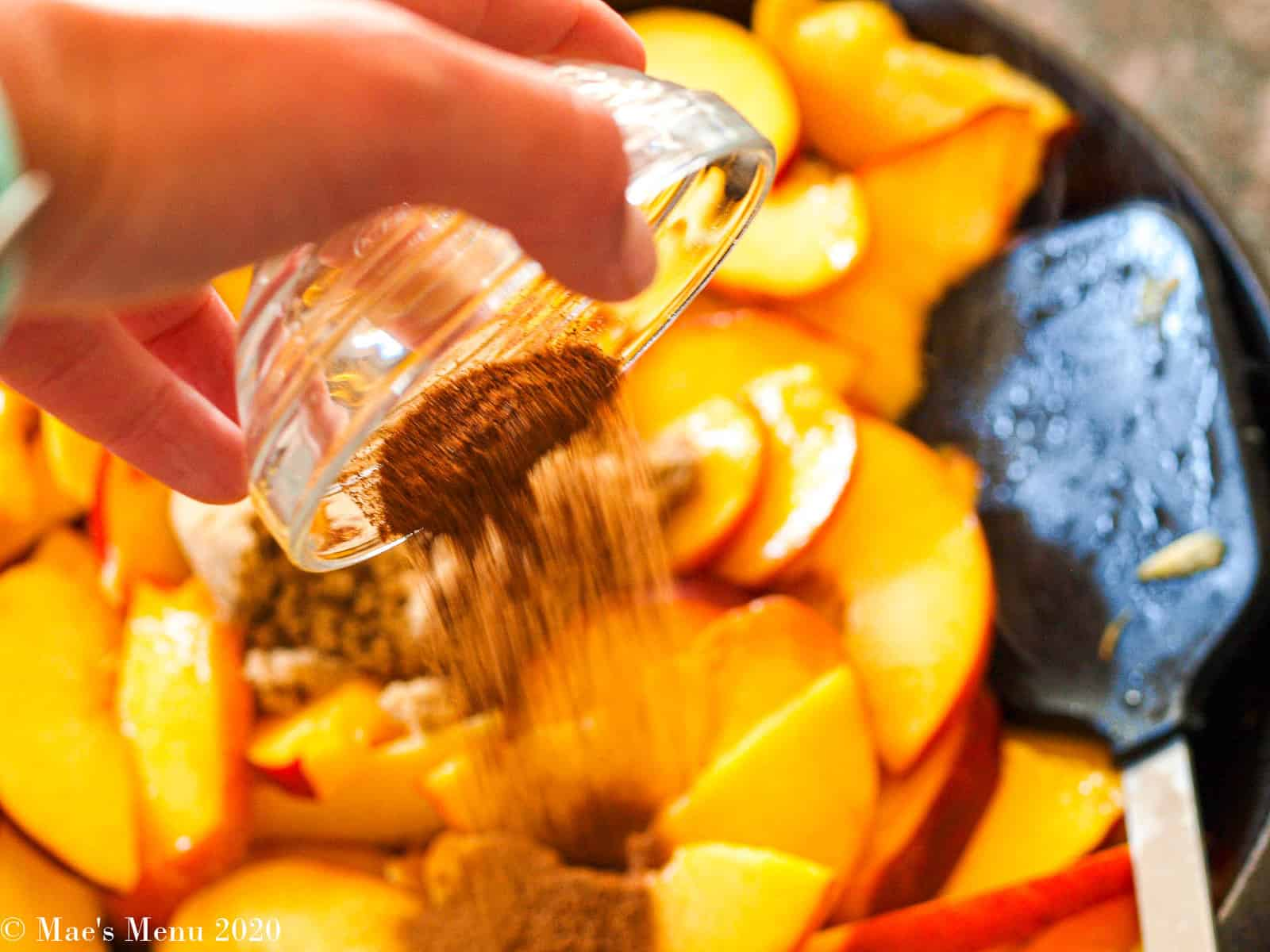 adding brown sugar and spices into the peaches