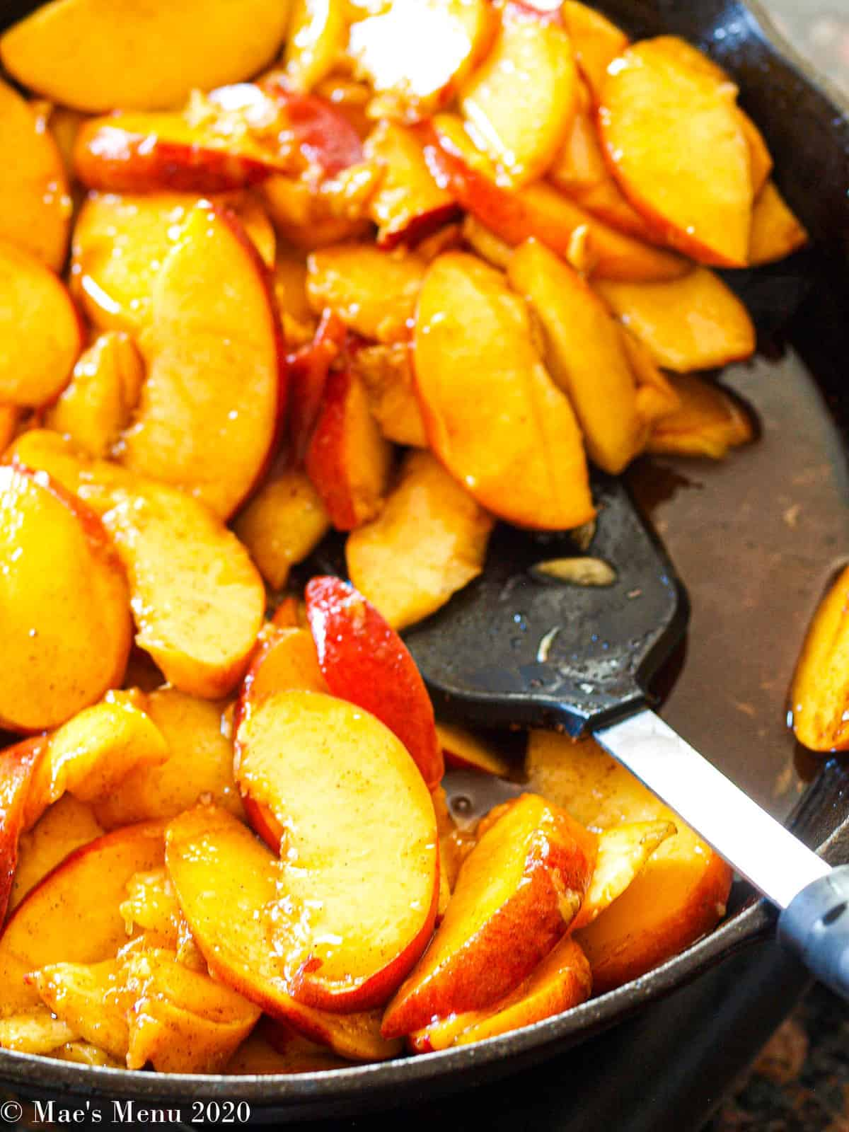 peaches and a spatula in a cast iron skillet