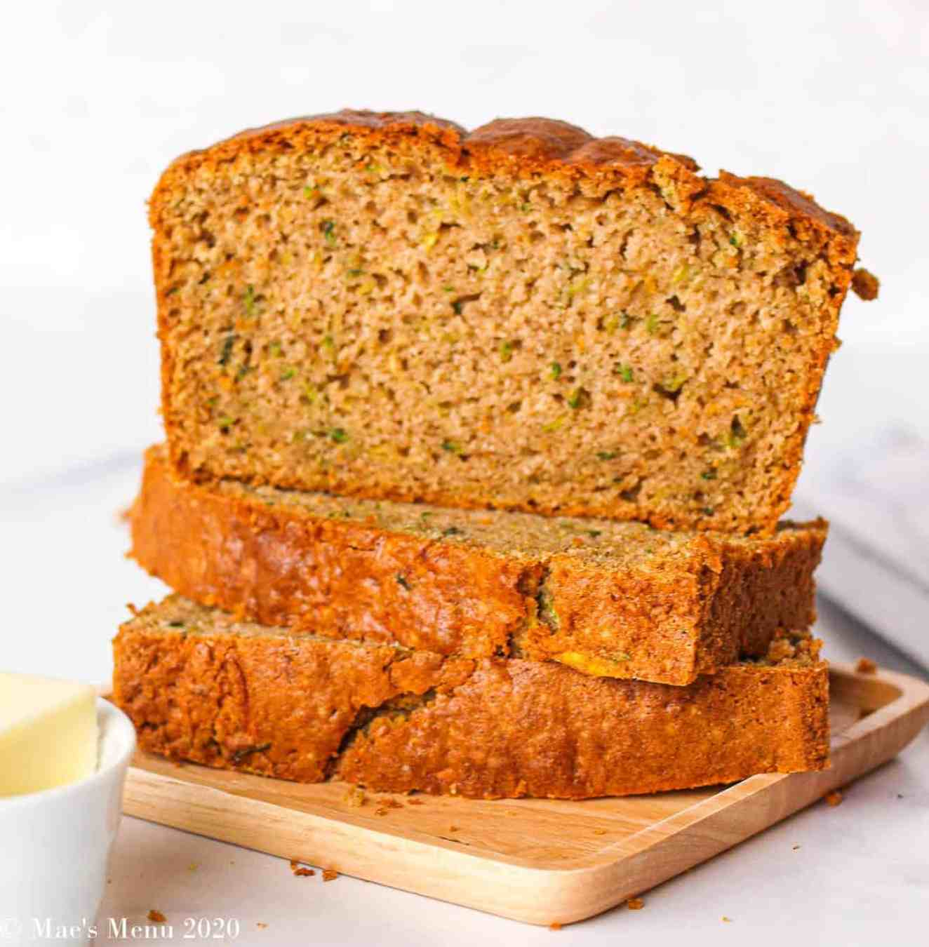 Two pieces of zucchini bread stacked on their side with a piece of bread sitting on top.