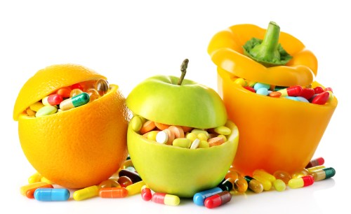 Orange fruit, apple and bell-pepper and colorful pills, isolated on white