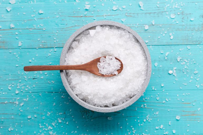 sea salt in stone bowl on wooden background