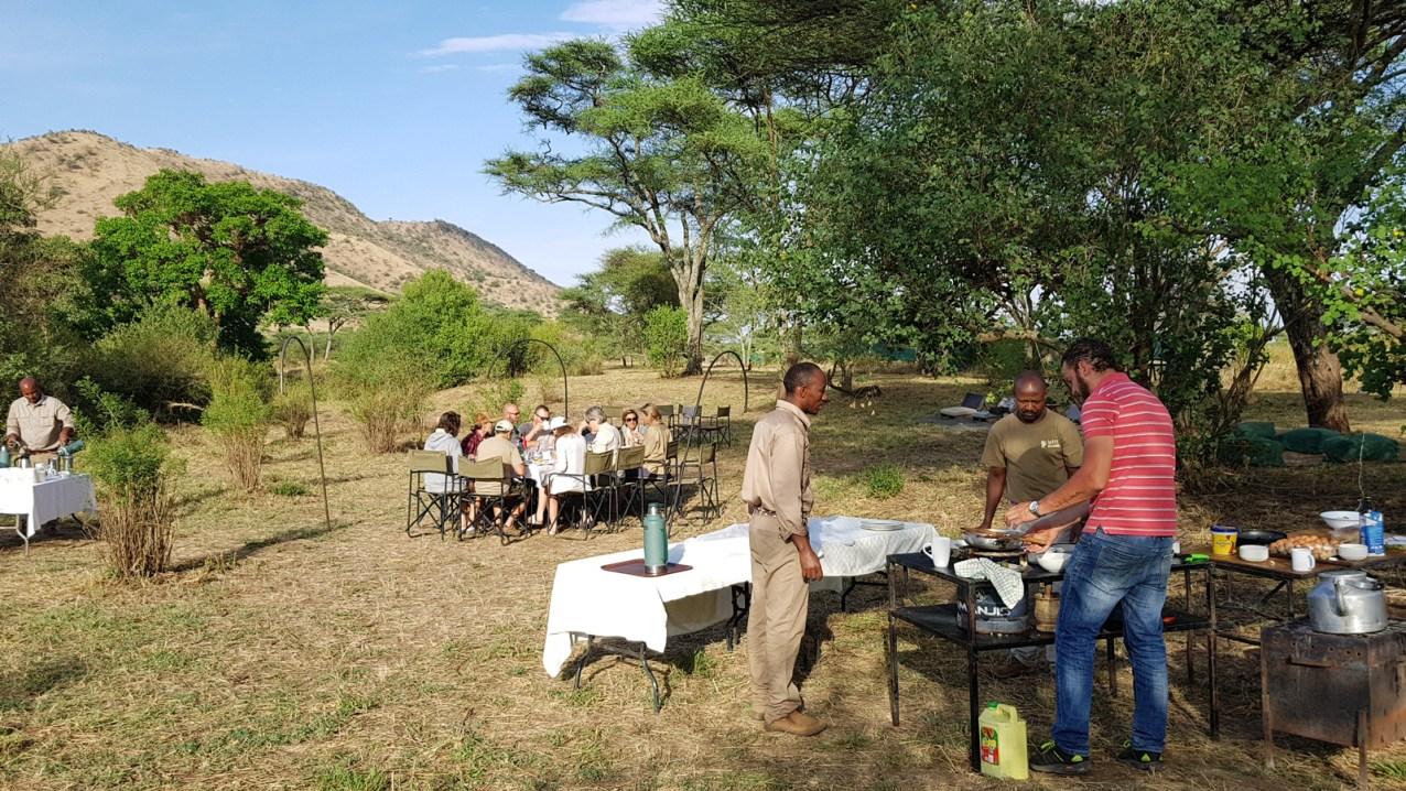Walking safari guests enjoying breakfast in Serengeti