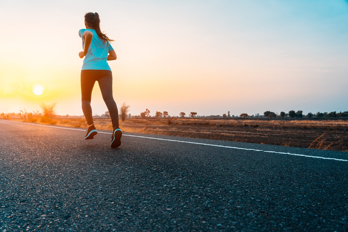 ragazza che corre al tramonto in campagna - mindful running: cos'è e quali sono i benefici