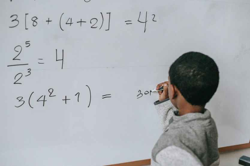 concentrated black kid doing sums