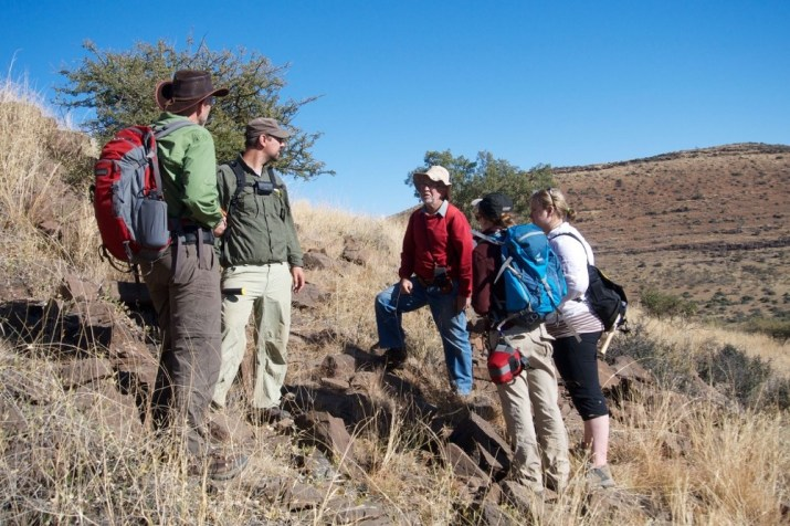 Five scientists stand wearing backpacks on a South African rocky hillside as part of a fossil dig. Photo/Andrew Czaja