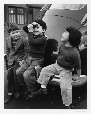 Three children sit on the back of a car.