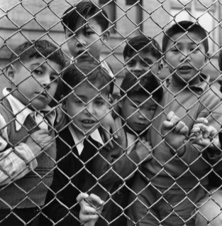Children gather behind a chainlink fence look curiously at the camera.
