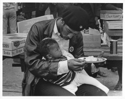 Black Panther Party member feeds his baby son.