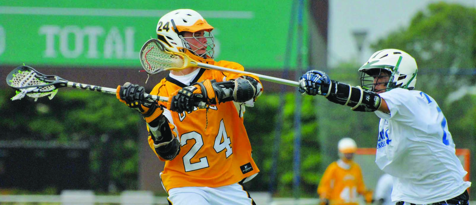 Two lacrosse players lunge for ball
