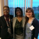 Three women pose in front of window at political science reception