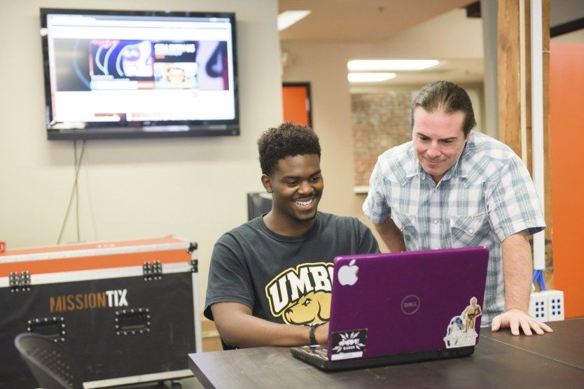 UMBC student on laptop assisted by man