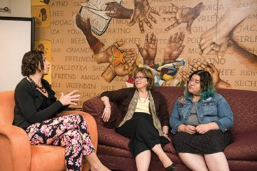 The women center panel with three women sitting on couches