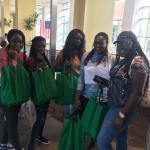 Group of female students posing with green care packages